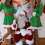 Santa with cheerful elves and child